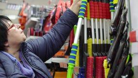 Μια ώριμη γυναίκα επιλέγει μια βούρτσα με τη μεταλλουργική ξύστρα στην υπεραγορά απόθεμα βίντεο