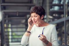 Μια ώριμη γυναίκα που μιλά στο κινητό τηλέφωνο που ζαλίζεται από αυτό που ακούει στοκ εικόνες