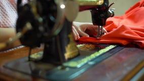 Μια Seamstress εργασία γυναικών για μια εκλεκτής ποιότητας ράβοντας μηχανή φιλμ μικρού μήκους