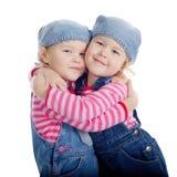 Μικρά δίδυμα κορίτσια που απομονώνονται στο άσπρο υπόβαθρο Στοκ Φωτογραφίες