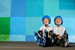 Μικρά αθλητικά αγόρια του Yong στη συνεδρίαση κυλίνδρων ενάντια στον μπλε τοίχο γκράφιτι Στοκ Εικόνα