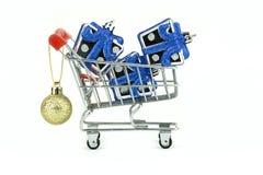 Μικρά ασημένια κιβώτια δώρων στο μικρό κάρρο αγορών με τη χρυσή λαμπρή σφαίρα για το φεστιβάλ, που απομονώνεται με το ψαλίδισμα τ στοκ φωτογραφίες