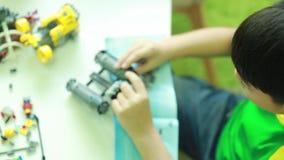 Μικρά ασιατικά παιδιά που παίζουν με τους φραγμούς απόθεμα βίντεο