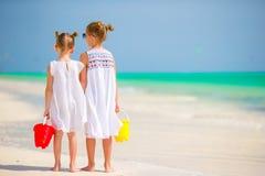 Μικρά λατρευτά κορίτσια με τα παιχνίδια παραλιών στην τροπική παραλία Στοκ Φωτογραφία