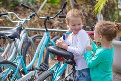 Μικρά λατρευτά κορίτσια που έχουν τη διασκέδαση κοντά στα ποδήλατα επάνω Στοκ εικόνες με δικαίωμα ελεύθερης χρήσης
