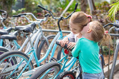 Μικρά λατρευτά κορίτσια που έχουν τη διασκέδαση κοντά στα ποδήλατα επάνω Στοκ Φωτογραφία