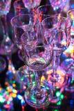 Μικρά γυαλιά ηδύποτου κρυστάλλου με το ζωηρόχρωμες υπόβαθρο και την αντανάκλαση Στοκ εικόνες με δικαίωμα ελεύθερης χρήσης