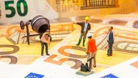 Μικρά ειδώλια που εργάζονται σκληρά σε νέα 50 ευρο- τραπεζογραμμάτια στοκ εικόνες