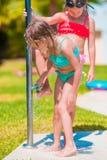 Μικρά ευτυχή κορίτσια κάτω από το ντους παραλιών στην τροπική παραλία Στοκ εικόνα με δικαίωμα ελεύθερης χρήσης