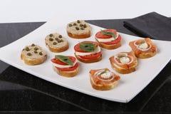 Μικρά καναπεδάκια με τον τόνο και την κάπαρη, ντομάτα και mozarella, σολομός και κρεμμύδια στοκ εικόνες