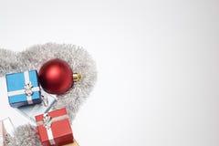 Μικρά κιβώτια για το δώρο Χριστουγέννων, τις σφαίρες Χριστουγέννων και tinsel Χριστουγέννων στο λευκό Στοκ Εικόνες