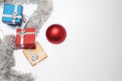Μικρά κιβώτια για το δώρο Χριστουγέννων, τις σφαίρες Χριστουγέννων και tinsel Χριστουγέννων στο λευκό Στοκ εικόνα με δικαίωμα ελεύθερης χρήσης