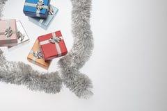 Μικρά κιβώτια για το δώρο Χριστουγέννων, τις σφαίρες Χριστουγέννων και tinsel Χριστουγέννων στο λευκό Στοκ εικόνες με δικαίωμα ελεύθερης χρήσης