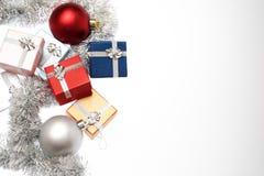 Μικρά κιβώτια για το δώρο Χριστουγέννων, τις σφαίρες Χριστουγέννων και tinsel Χριστουγέννων στο λευκό Στοκ Φωτογραφία