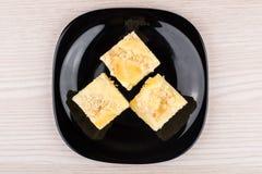 Μικρά κομμάτια της πίτας στο μαύρο πιάτο γυαλιού, τοπ άποψη Στοκ Εικόνες