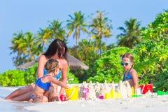 Μικρά κορίτσια και ευτυχές παιχνίδι μητέρων με την παραλία Στοκ Εικόνες