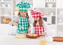 Μικρά κορίτσια με τα καπέλα αρχιμαγείρων που προετοιμάζουν ένα κέικ Στοκ εικόνα με δικαίωμα ελεύθερης χρήσης