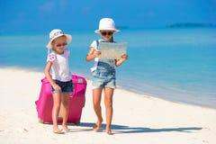 Μικρά κορίτσια με τη μεγάλους βαλίτσα και το χάρτη σε τροπικό Στοκ Φωτογραφίες