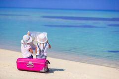 Μικρά κορίτσια με τη μεγάλους βαλίτσα και το χάρτη στην τροπική παραλία Στοκ Εικόνες