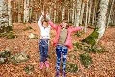 Μικρά κορίτσια που έχουν τη διασκέδαση με τα laves το φθινόπωρο σε Biogradska Gora στοκ εικόνες