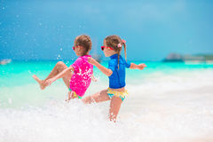 Μικρά κορίτσια που έχουν τη διασκέδαση στην τροπική παραλία κατά τη διάρκεια του παιχνιδιού θερινών διακοπών μαζί στα ρηχά νερά Στοκ Εικόνα