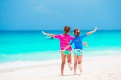 Μικρά κορίτσια που έχουν τη διασκέδαση στην τροπική παραλία κατά τη διάρκεια του παιχνιδιού θερινών διακοπών μαζί στα ρηχά νερά Στοκ εικόνες με δικαίωμα ελεύθερης χρήσης