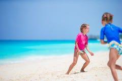 Μικρά κορίτσια που έχουν τη διασκέδαση στην τροπική παραλία κατά τη διάρκεια του παιχνιδιού θερινών διακοπών μαζί στα ρηχά νερά Στοκ Εικόνες