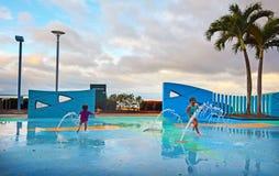 Μικρά κορίτσια που έχουν τη διασκέδαση Esplanade τύμβων στο δημόσιο πάρκο νερού μέσα Στοκ εικόνα με δικαίωμα ελεύθερης χρήσης