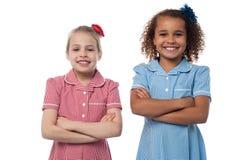 Μικρά κορίτσια που θέτουν με τα όπλα που διασχίζονται Στοκ Εικόνες