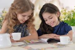 Μικρά κορίτσια που διαβάζουν ένα περιοδικό Στοκ Εικόνες