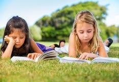 Μικρά κορίτσια που διαβάζουν τα βιβλία στη χλόη Στοκ Φωτογραφία