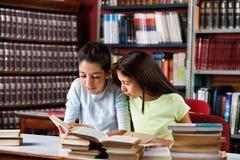Μικρά κορίτσια που διαβάζουν το βιβλίο μαζί στη βιβλιοθήκη Στοκ εικόνα με δικαίωμα ελεύθερης χρήσης