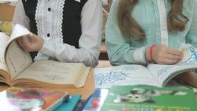 Μικρά κορίτσια που κάθονται στις σελίδες κτυπημάτων γραφείων του βιβλίου απόθεμα βίντεο