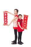 Μικρά κορίτσια που παρουσιάζουν couplets για το ευτυχές κινεζικό νέο έτος στοκ εικόνα με δικαίωμα ελεύθερης χρήσης