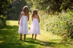 Μικρά κορίτσια που περπατούν κατά μήκος της πορείας στοκ εικόνα