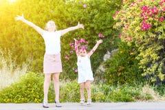 Μικρά κορίτσια που ρίχνουν τα ρόδινα πέταλα από πάνω στοκ φωτογραφίες