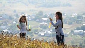 Μικρά κορίτσια που φυσούν τις φυσαλίδες σαπουνιών φιλμ μικρού μήκους