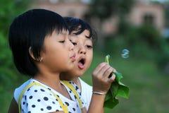 Μικρά κορίτσια που φυσούν τις φυσαλίδες που εκκρίνονται από το φύλλο Jatropha Στοκ εικόνες με δικαίωμα ελεύθερης χρήσης