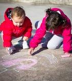 Μικρά κορίτσια που χρωματίζουν με την κιμωλία Στοκ εικόνα με δικαίωμα ελεύθερης χρήσης