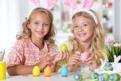 Μικρά κορίτσια που χρωματίζουν τα αυγά Πάσχας Στοκ φωτογραφία με δικαίωμα ελεύθερης χρήσης