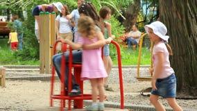 Μικρά κορίτσια στον εύθυμος-πηγαίνω-κύκλο φιλμ μικρού μήκους