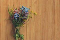 Μικρά μπλε λουλούδια άνοιξη σε ένα καφετί υπόβαθρο, επιστολή φακέλων Στοκ Εικόνα