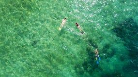 Μικρά παιδιά που κολυμπούν με αναπνευτήρα με τη μητέρα τους στοκ εικόνα με δικαίωμα ελεύθερης χρήσης