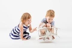 Μικρά παιδιά που παίζουν με τη συνεδρίαση αεροπλάνων παιχνιδιών εγγράφου στο φ Στοκ Φωτογραφία