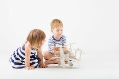 Μικρά παιδιά που παίζουν με τη συνεδρίαση αεροπλάνων παιχνιδιών εγγράφου στο φ Στοκ φωτογραφίες με δικαίωμα ελεύθερης χρήσης
