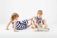 Μικρά παιδιά που παίζουν με τη συνεδρίαση αεροπλάνων παιχνιδιών εγγράφου στο φ Στοκ Εικόνες