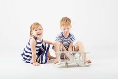 Μικρά παιδιά που παίζουν με τη συνεδρίαση αεροπλάνων παιχνιδιών εγγράφου στο φ Στοκ Εικόνα