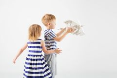 Μικρά παιδιά που παίζουν με το αεροπλάνο παιχνιδιών εγγράφου ενάντια σε ένα λευκό Στοκ Φωτογραφία