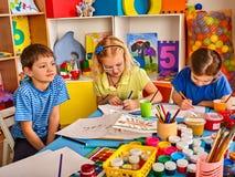 Μικρά παιδιά σπουδαστών που χρωματίζουν στη σχολική τάξη τέχνης Στοκ Φωτογραφία