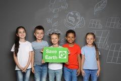Μικρά παιδιά σχολείου με τη ΓΗ SAVE αφισσών στοκ φωτογραφίες